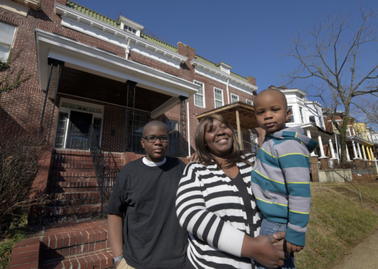 April Bradley, 33, is pictured with her sons Tayveon, 12 and Dominic, 3 in front of her home. With the help from Baltimore CASH Campaign, a financial literacy nonprofit, she saved enough with her tax refund and other refunds and savings to purchase a home outright. (Algerina Perna/Balitmore Sun/TNS)